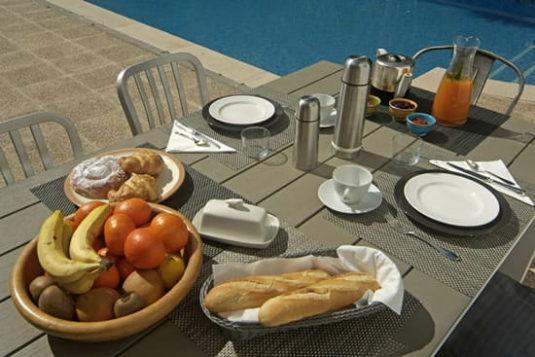 La prima colazione è servita a bordo piscina, tra i profumi e i colori del giardino