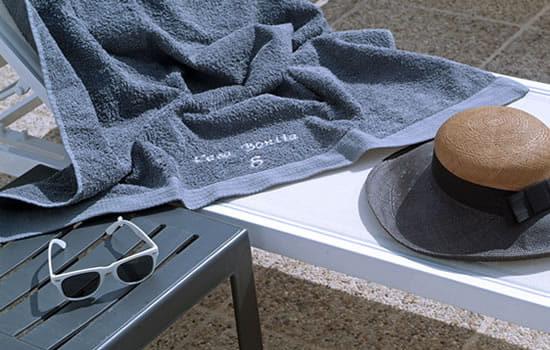 Una toalla gris está lista para ser utilizada en la piscina y sobre las tumbonas
